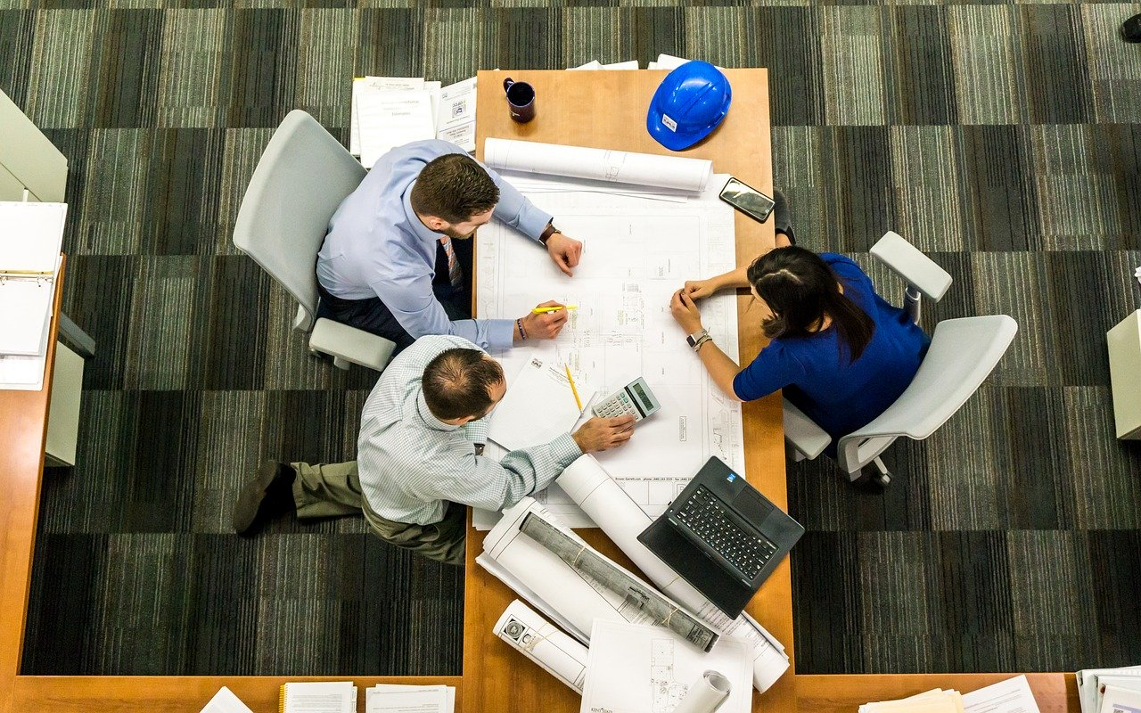 3 personnes assises autour d'un bureau qui travaillent sur un plan