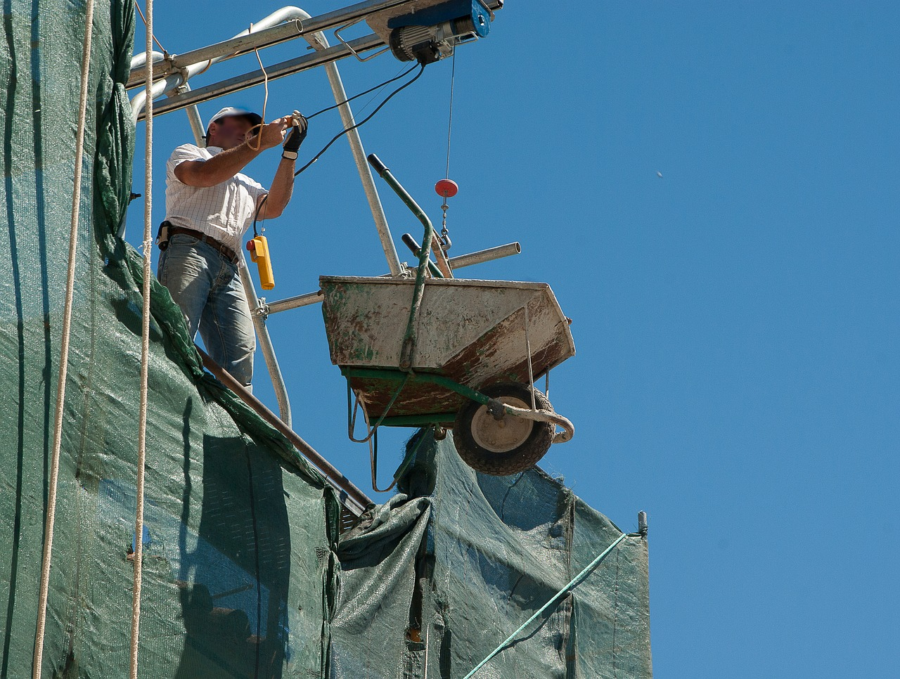 ouvrier de chantier qui fait monter une brouette grâce à des poulies