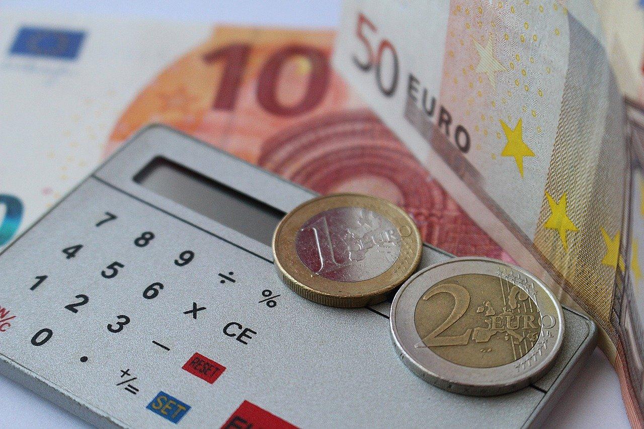 calculatrice sur laquelle des pièces de monnaie sont posées