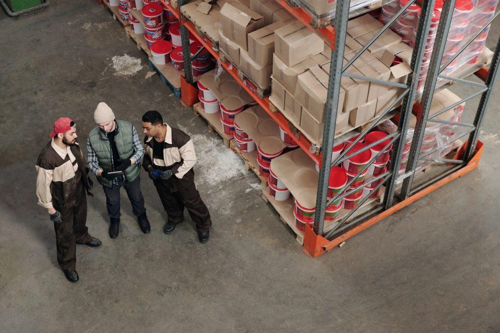 3 personnes qui discutent dans un entrepôt