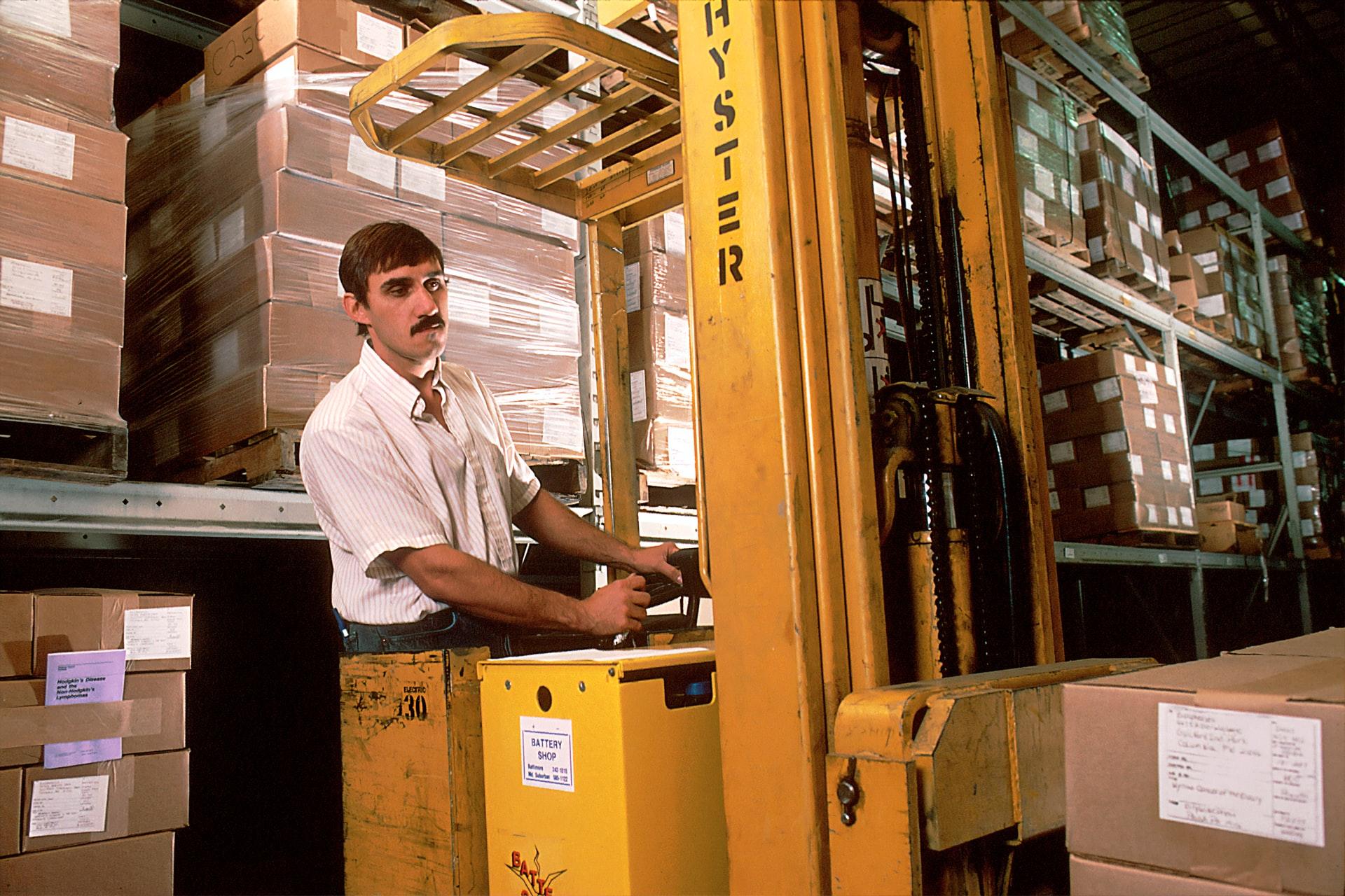 homme dans un entrepôt filmage palettes